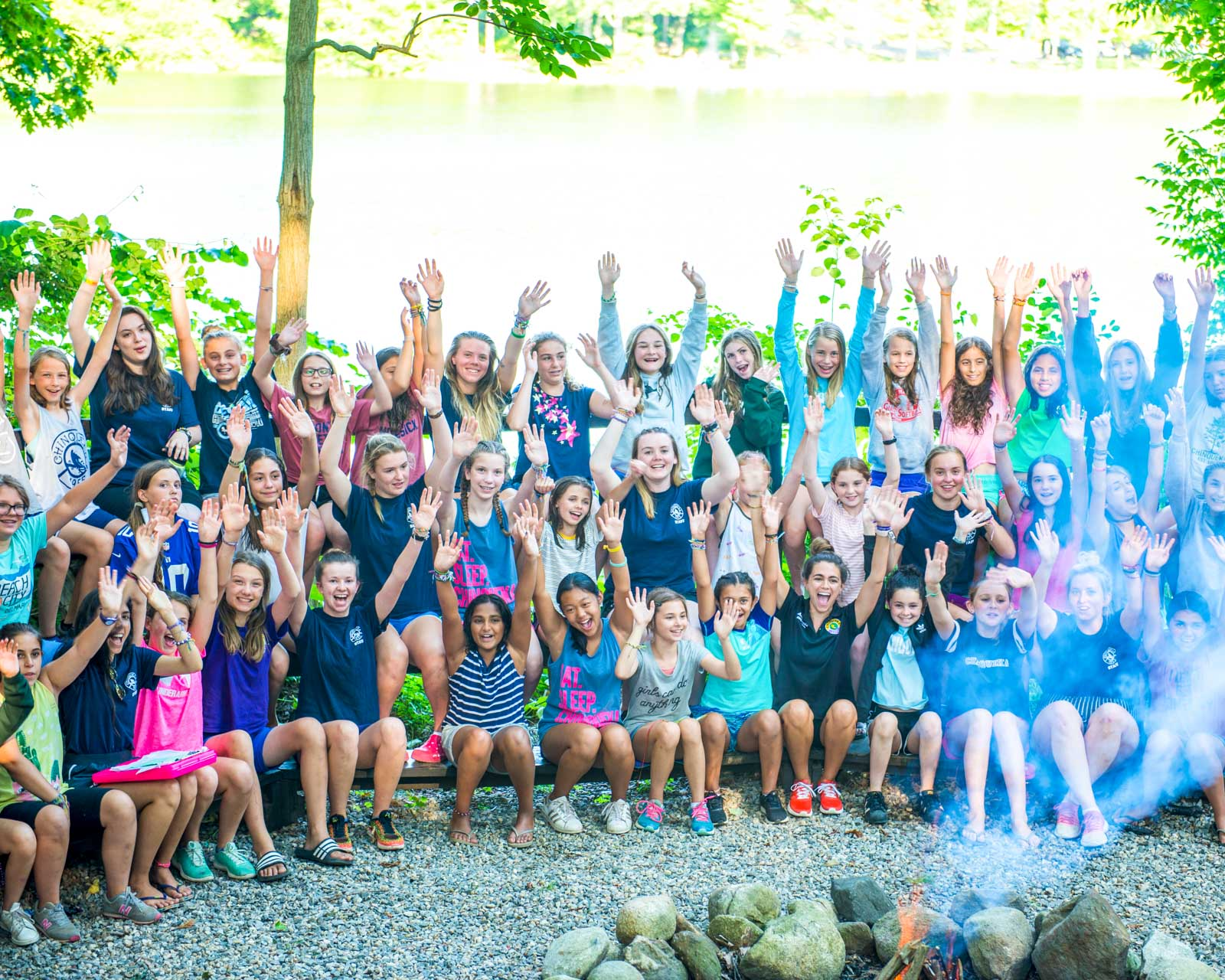 Group of campers hold arms up around campfire