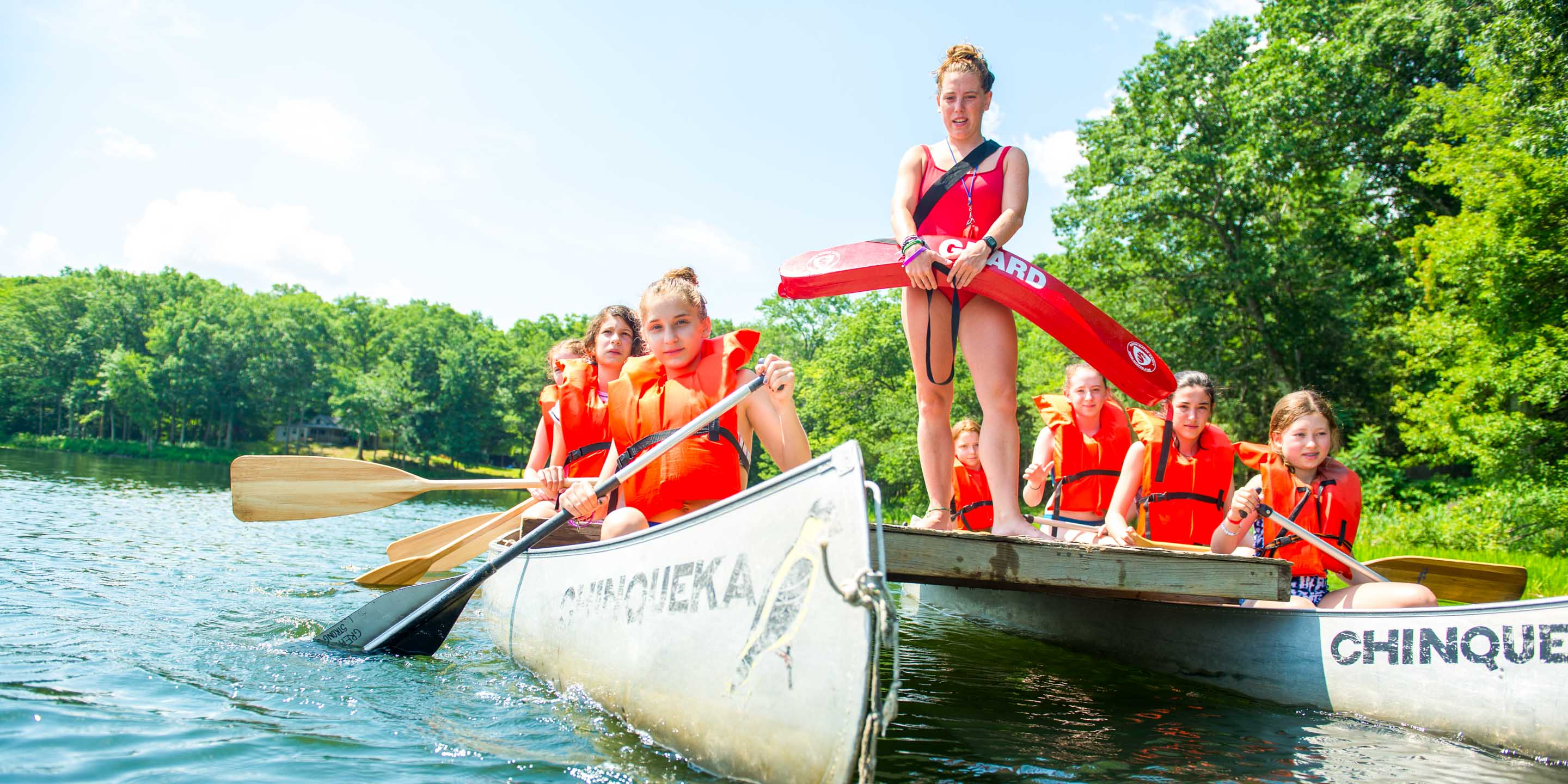 Life guard stands on canoe paddled by campers