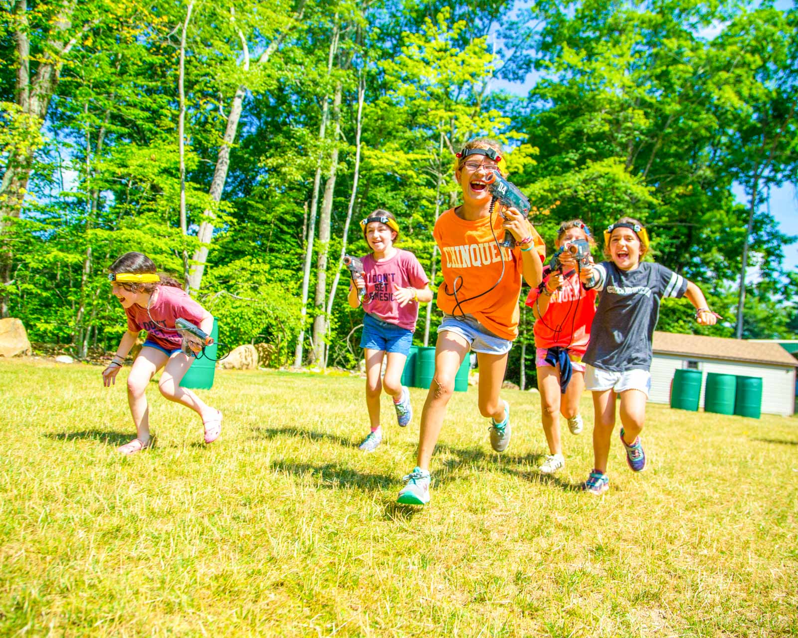 Campers run after each other playing laser tag