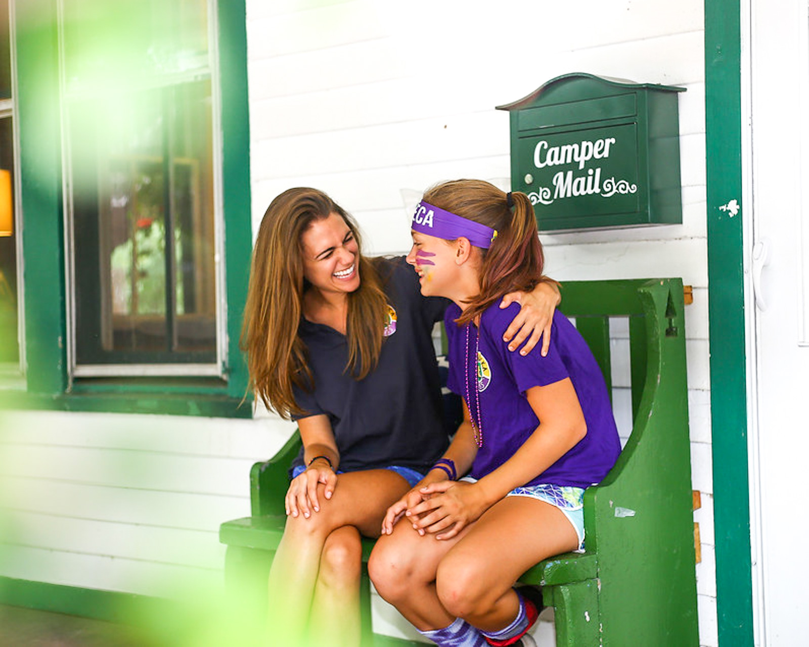 Camp director laughs with girl on porch bench
