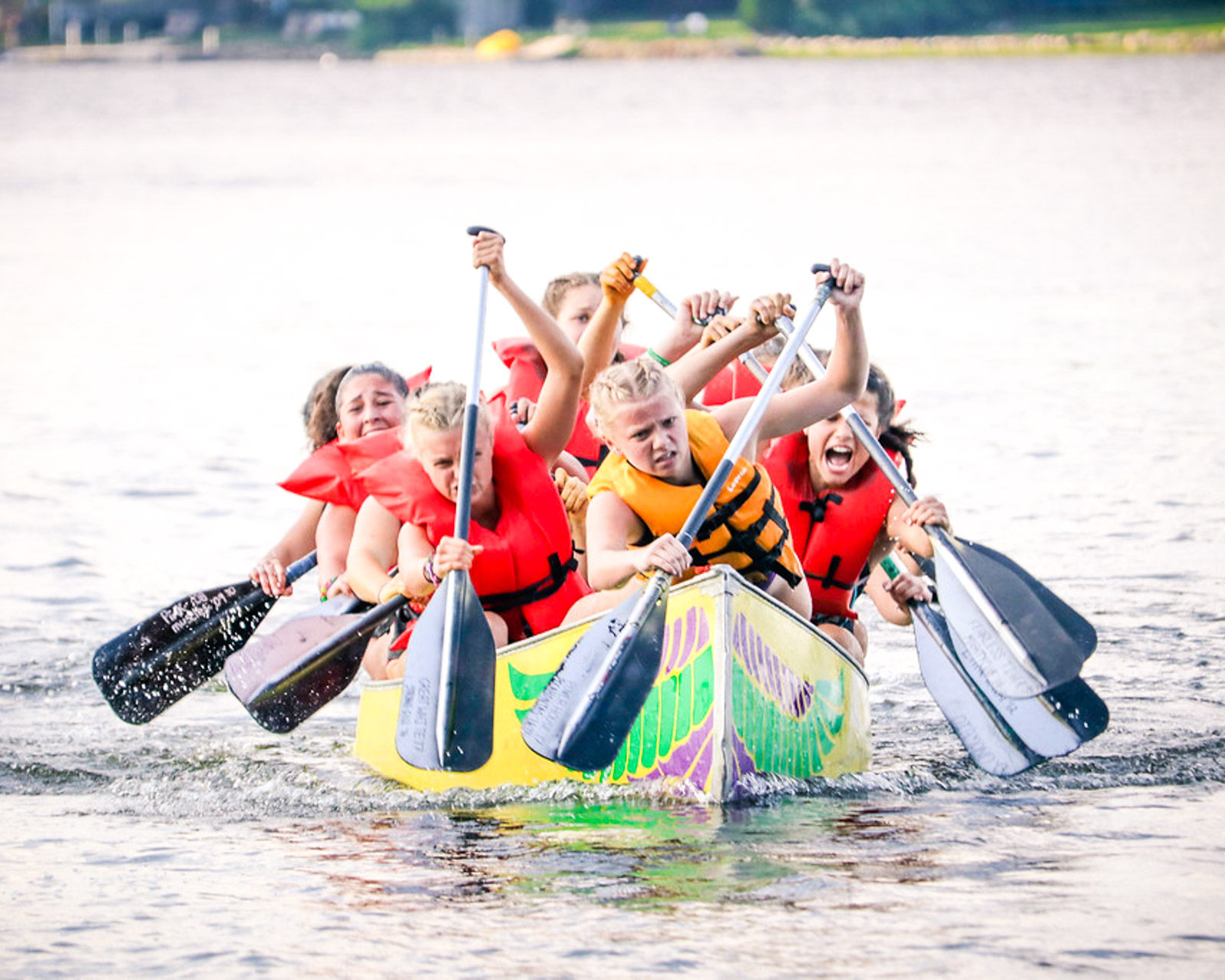 Group of girls paddles canoe toward camera